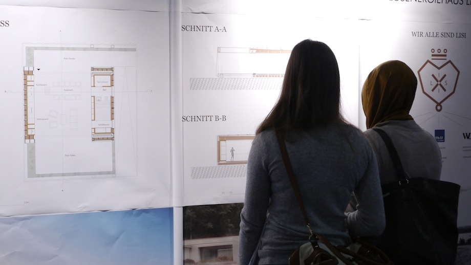 Two girls standing in front of LISI posters, studying the graphics.jpg