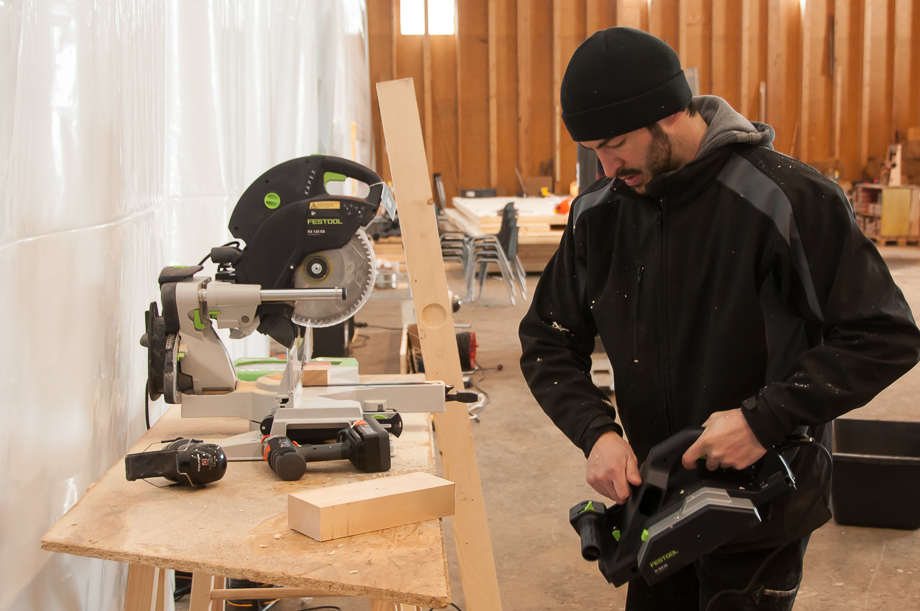 Johannes operating a rotary saw while wearing a hat