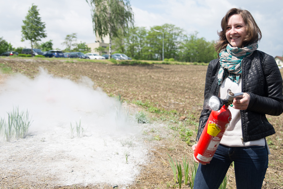 Kathi smiling with a fire extinguisher in her hand