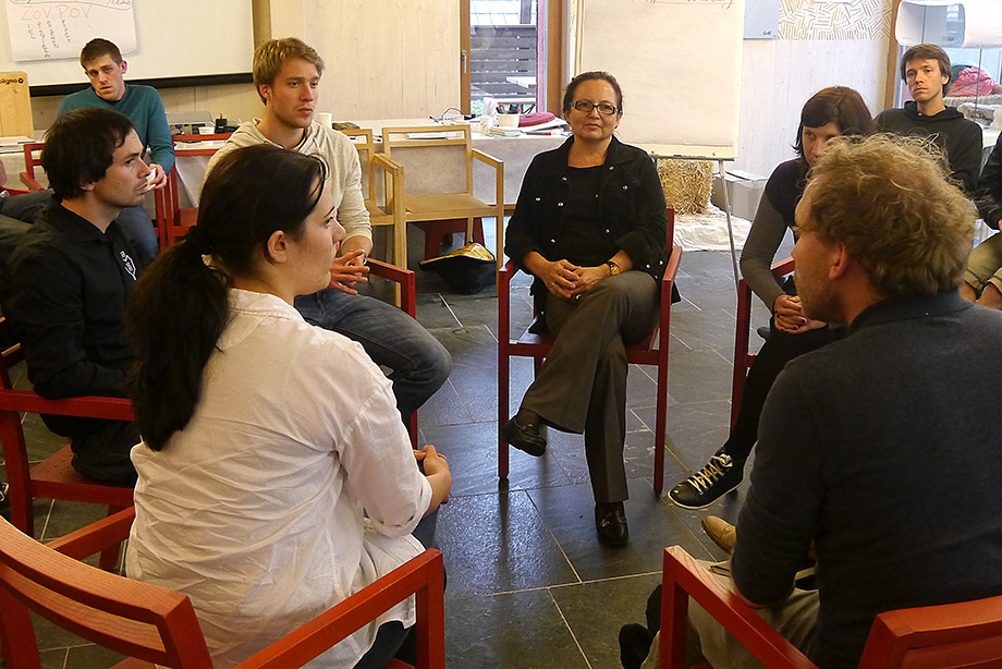 Students and teachers sit together to discuss current issues within the project