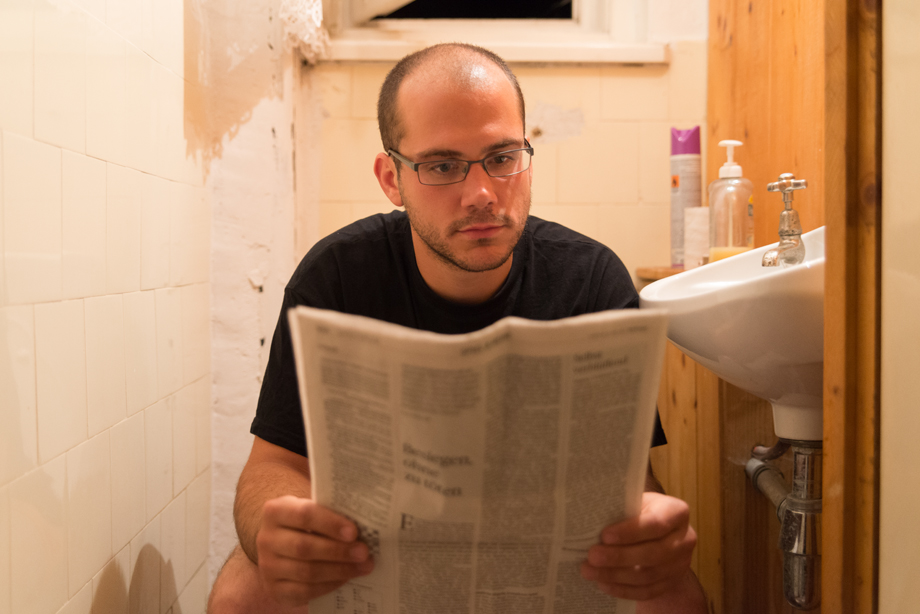 Rainer is sitting on the toilet and reading the newspaper