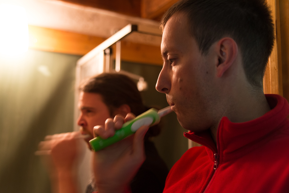 two Decathletes brushing their teeth in a tiny bathroom