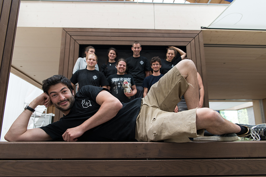 The team is posing in front of the finished house. Johannes is lying in the foreground.