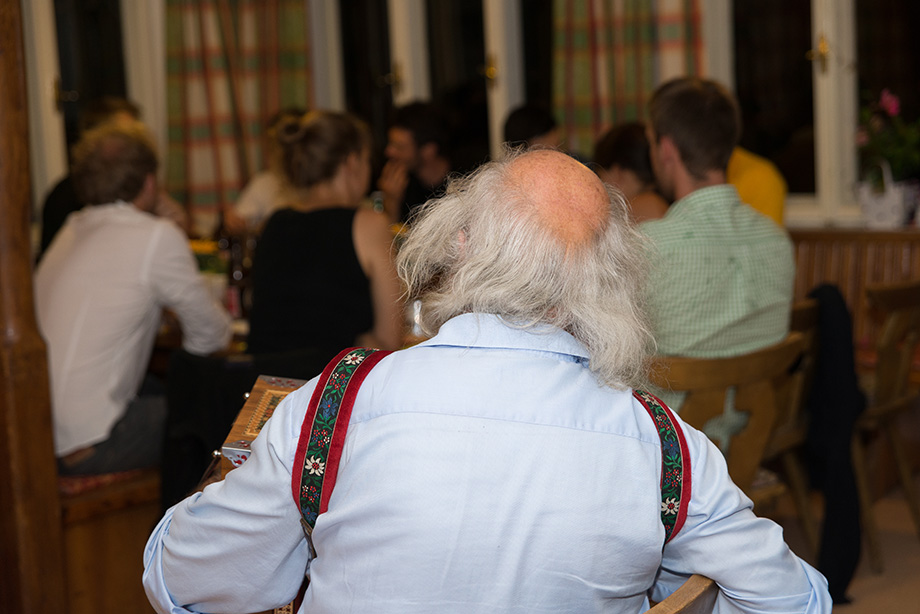 An old, greyhaired man seen from behind. In the background are decathletes.