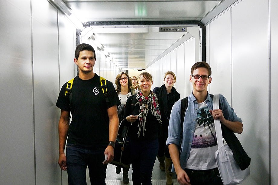 5 decathletes walking down a passenger bridge towards an airplane
