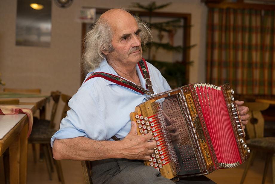 Same old man. He is playing the accordion.