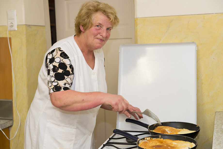 Here is the old man's wife. She is wearing a white apron and making pancakes.