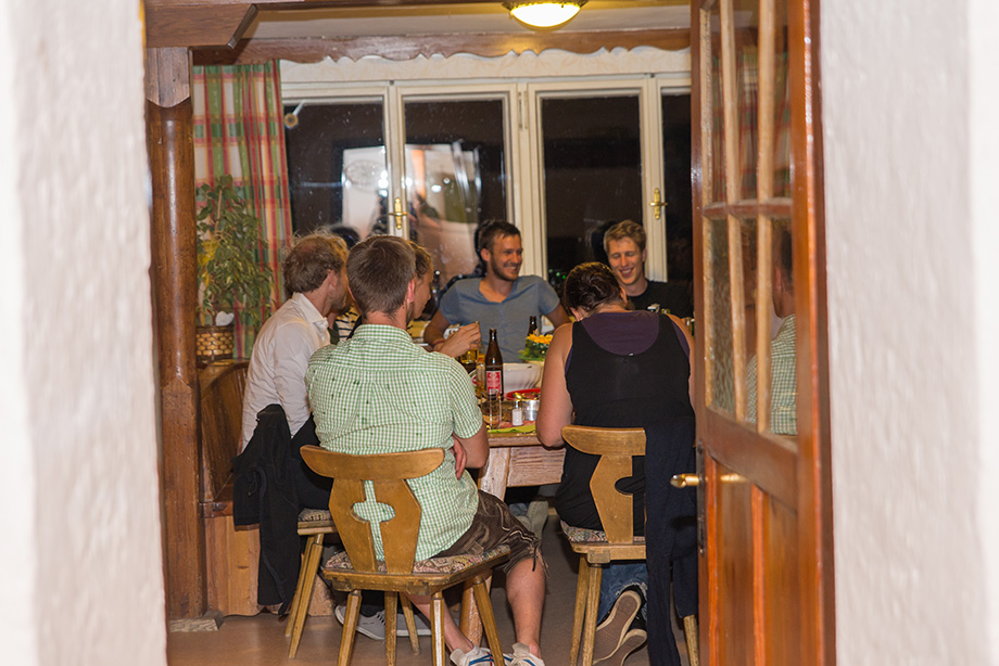 """""""Stube"""" is the name of the dining room in Alpine houses. The group has gathered around a table."""