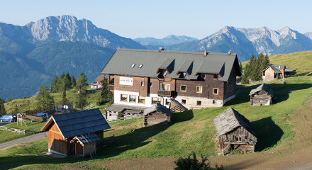 The house of the old man is situated on a mountain slope looking at a beautiful alpine landscape.
