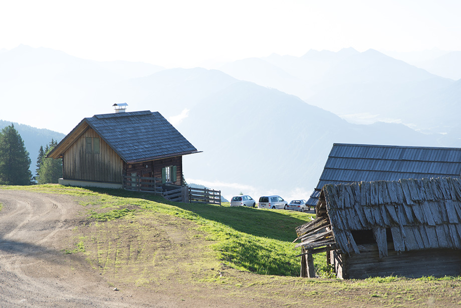 The two houses standing on a slope. In the distance, there are mountains.