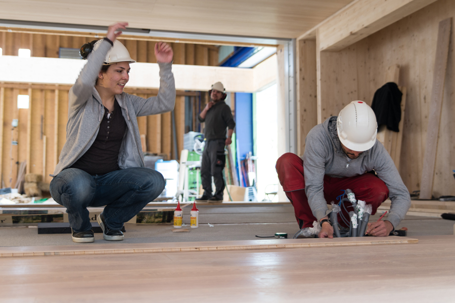 Two decathletes placing the parquet inside the living area.
