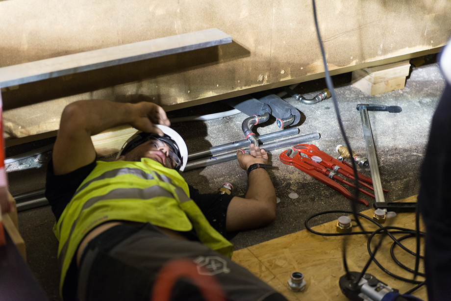 A decathlete lying on the floor installing something beneath the house.