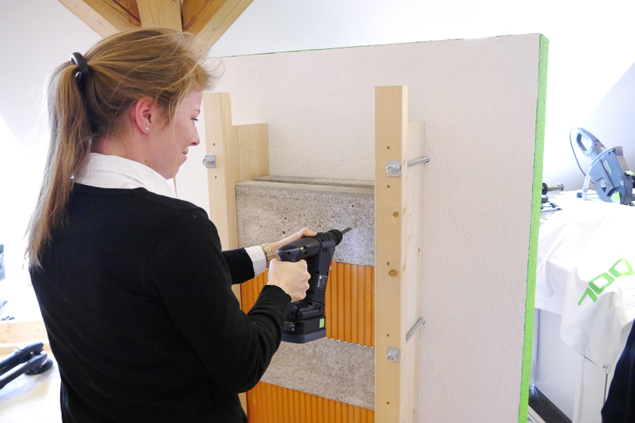 Sigrid is using a new drill, to drill a hole in a concrete wall.