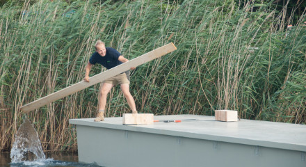 Decathlete Wolfgang is paddling on a pontoon. He is using a piece of wood.